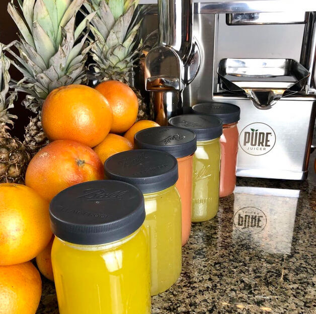 Orange juice, PURE juicer, and fruit